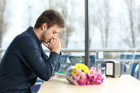 cancel: Sad man with bunch of flowers stood up in a date by his girlfriend in a coffee shop