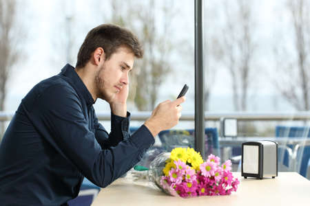 Sad man with a bouquet of flowers stood up in a date checking phone messages in a coffee shop Stok Fotoğraf