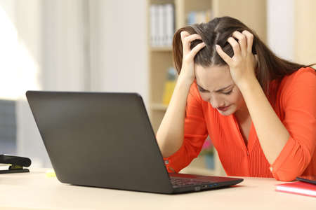 Verdrietig en wanhopig freelancer vrouwelijke werken op lijn met een laptop met haar handen op het hoofd zitten in een bureau of thuis interieur