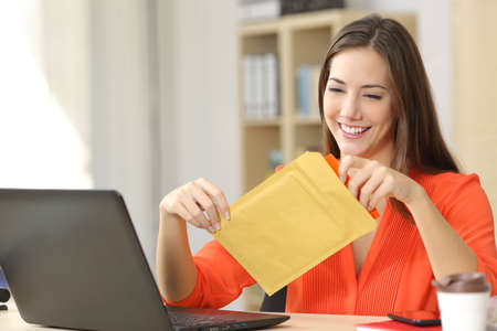 Freelancer opening a padded envelope in an office or home 免版税图像