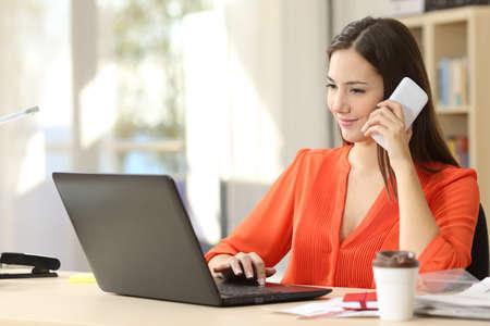 Hermosa mujer independiente trabajando en línea y hablando por teléfono y navegando en una computadora portátil en casa u oficina