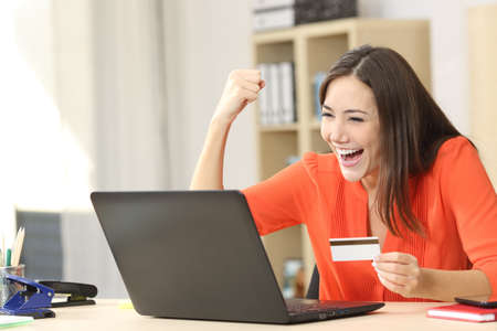 Euphoric shopper buying on line with a laptop and a credit card at home or office