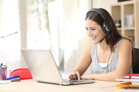 headset woman: Student talking in a video call on line with headsets and a laptop in a desk at home Stock Photo