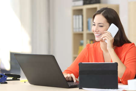 Entrepreneur working on line with multiple devices in a desk in a little office or home