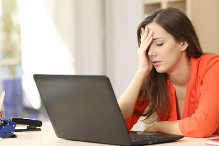 profesional independiente con exceso de trabajo cansado que trabaja con un ordenador portátil en una oficina o en el hogar