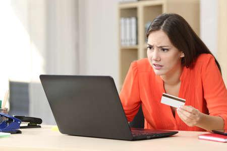 Gelegenheits Käufer besorgt mit Problemen auf der Linie mit einer Kreditkarte zu kaufen und einen Laptop in einem kleinen Büro oder zu Hause