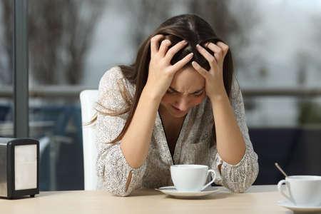 pareja enojada: Triste y deprimido mujer sola en un bar solitario después de una ruptura con un día de invierno al aire libre de las lluvias en el fondo