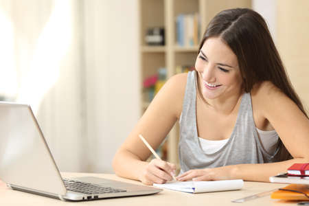 deberes: El estudiante feliz de aprendizaje en línea y tomando notas en un bloc de notas que hace la preparación mirando la pantalla del ordenador portátil en un escritorio en el país