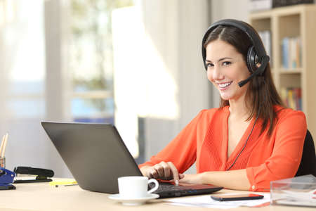 Beautiful freelancer female posing and working on line with headset with mic and looking at camera in a little office desktop or home Stock Photo