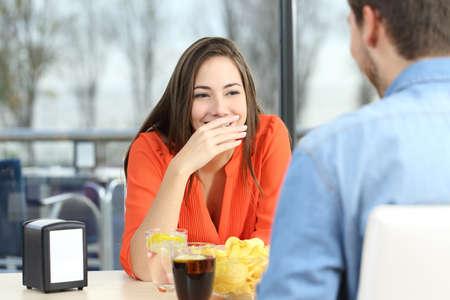 Mujer que cubre su boca para ocultar la sonrisa o el mal aliento durante una cita en una cafetería con una ventana en el fondo