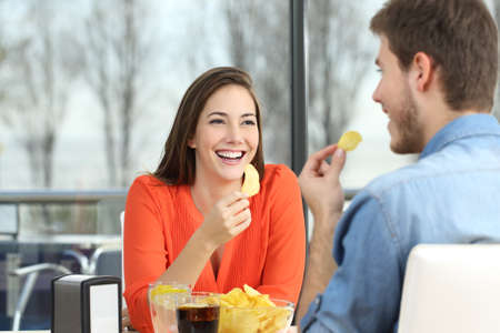 fast food restaurant: Cheerful couple talking and eating chip potatoes looking each other dating inside a coffee shop with an exterior background Stock Photo