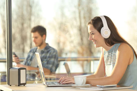 Side view of a beautiful female working on line with headphones typing in a laptop in a restaurant indoor with a window in the background and people outdoors