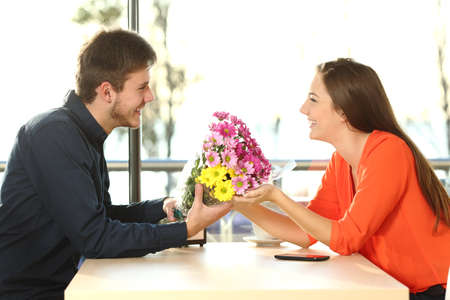 encounter: Profile of a couple dating and looking each other with a man giving a bouquet of flowers to his partner in a coffee shop