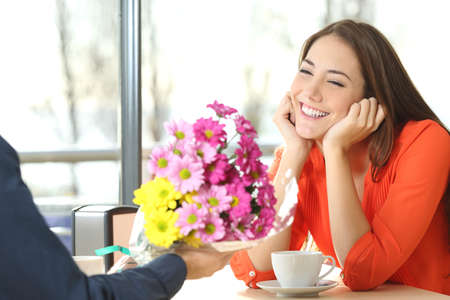 Couple dating and boyfriend giving a bouquet of flowers to his candid girlfriend in a coffee shop Foto de archivo