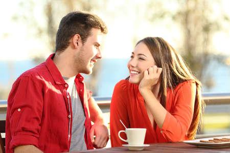 dos fecha Candid enamoramiento que ligan en una terraza mirando el uno al otro con ternura pensar que besar