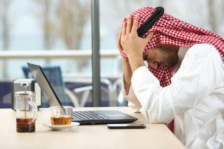 Profil eines verzweifelten und allein arabischen saudi Mann mit einem Laptop online in einem Café mit einem Fenster im Hintergrund. Konkurs Konzept