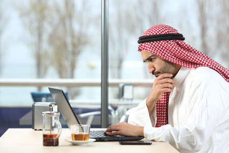 working on laptop: Side view of an arab saudi man worried working with a laptop in a coffee shop interior with the terrace in the background