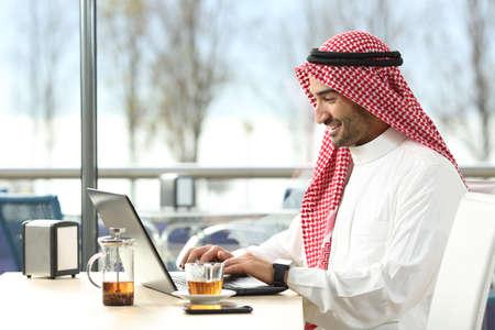 노트북과 스마트 워치 커피 숍 또는 백그라운드에서 창 및 야외 테라스가있는 호텔 바 온라인 작업 아랍 사우디 남자