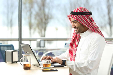 Arab saudi man working online with a laptop and smartwatch in a coffee shop or an hotel bar with a window and outdoor terrace in the background
