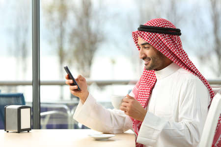 Side view of an arab man texting in a smart phone in a coffee shop with a window with a sunny day in the background