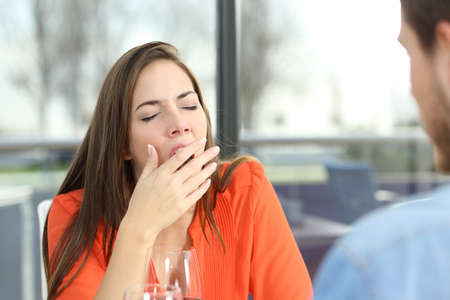 yawing: Woman bored or tired yawing in a bad date in a coffee shop with a window in the background Stock Photo