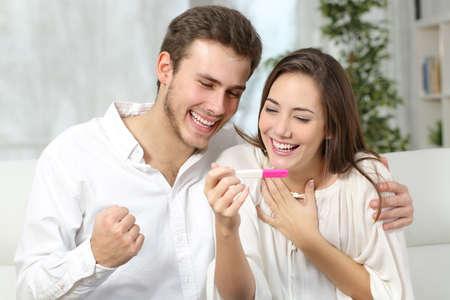 Gelukkig opgewonden paar het maken van positieve zwangerschapstest en het vieren