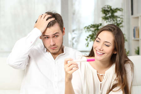 Not ready worried man checking a pregnancy test with his excited wife sitting on a couch at home