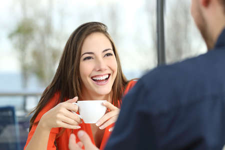 Happy woman dating in a coffee shop looking at her partner and holding a cup