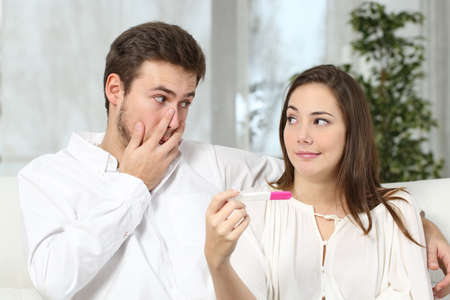 despaired: Worried couple or marriage looking each other making a pregnancy test at home. Contraceptive failure concept