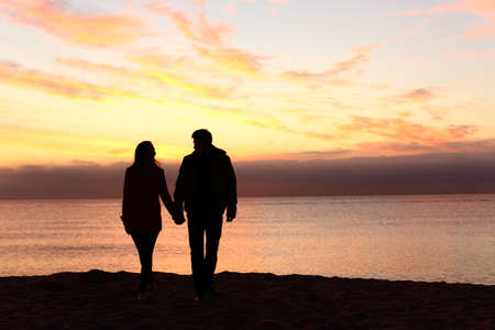 Front view of a full body of couple silhouettes holding hands and walking together looking each other in a date at sunset on the beach Banco de Imagens
