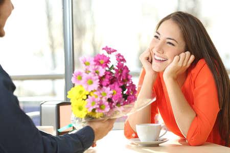 Mujer franca a salir en una tienda de café y mirando a su novio que le da un ramo de flores
