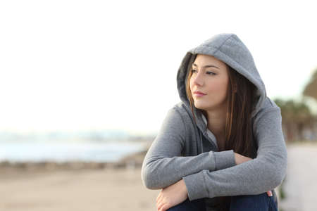 Portrait of a longing pensive teenager sitting on the beach looking away at the horizon in the morning Stock Photo