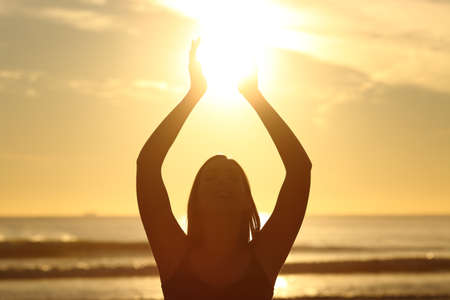 Front view of a back light of faithful woman silhouette holding sun on the beach at sunrise with a warm background Stock Photo