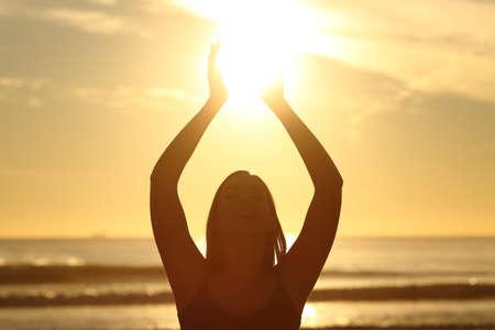 Vista frontal de una luz de fondo de la mujer fiel silueta sosteniendo el sol en la playa al amanecer con un fondo cálido Foto de archivo
