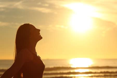 暖かい日の出太陽の前に深い新鮮な空気を呼吸の女性シルエットのバックライトの側面図