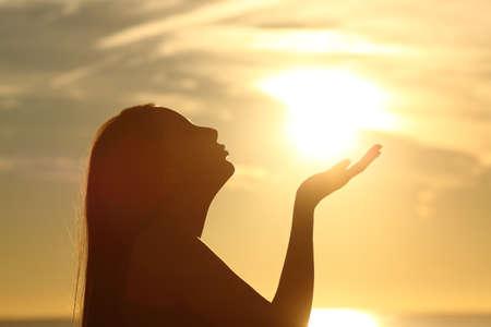 Vista lateral de uma silhueta de mulher beijando o sol na praia ao pôr do sol Foto de archivo