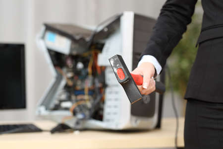 out of control: Computer absolutely destroyed by a hot-tempered businesswoman hand holding a hammer