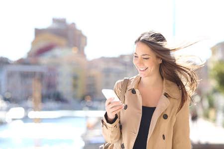 Happy schöne Frau zu Fuß und Schreiben oder Lesen von SMS-Nachrichten auf der Linie auf einem Smartphone während der Wind ihr Haar in einer Straße von einem Hafen Urbanisierung bewegt