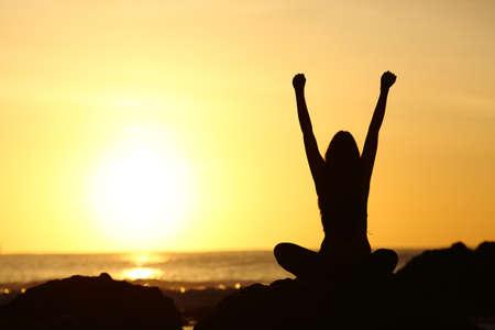 무기를 양육하고 백그라운드에서 바다와 해변에서 일출 오렌지 태양을 찾고 흥분된 행복 한 여자 실루엣의 다시보기