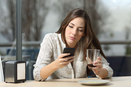 Angry woman stood up in a date in a coffee shop searching for messages and lost calls in a smart phone Banco de Imagens