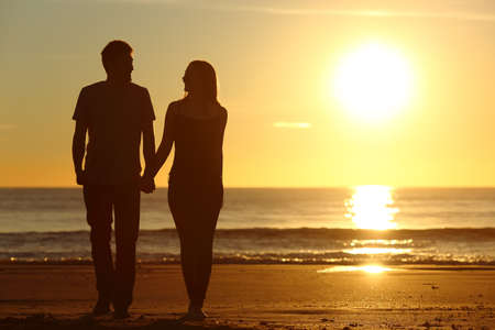 Front view of a full body of a couple silhouette walking together on the beach at sunset in summer