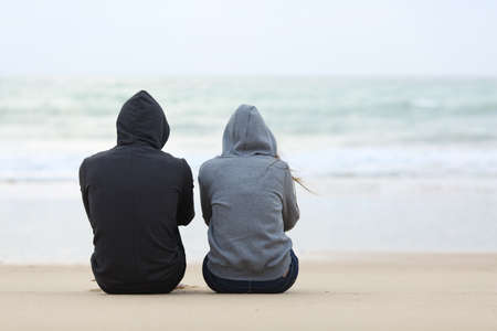 Back view of two sad teenagers sitting on the sand of the beach and looking at horizon in a bad weather day Stock Photo