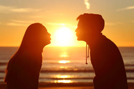 other side of: Side view of a couple silhouette of teenagers kissing the sun with love at sunset on the beach with the horizon in the background Stock Photo