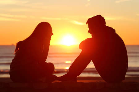 Side view of full body of two friends or couple silhouette of teens facing at sunset on the beach with the sun in the middle