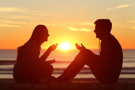 couples in love: Side view of a full body of two friends or couple silhouette of teens sitting and talking at sunrise on the beach with the sun in the middle