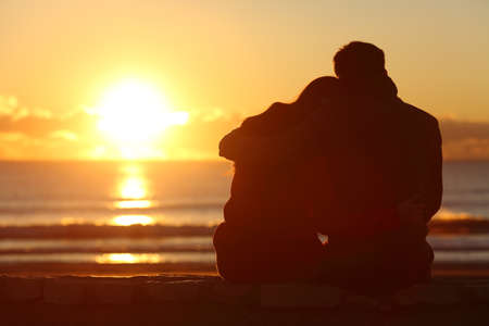 Back view of a couple silhouette watching sun at sunset on the beach in winter with a warmth light Stock Photo