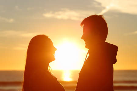 love at first sight: Couple standing looking each other and falling in love with the sun in the middle at sunset in the beach