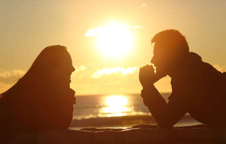 a meeting with a view to marriage: Profile of a couple silhouette looking each other at sunset on the beach with the sun in the middle and a warmth light