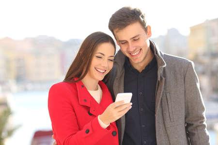 야외에서 겨울에 미디어 콘텐츠를보고있는 스마트 폰을 공유하는 커플