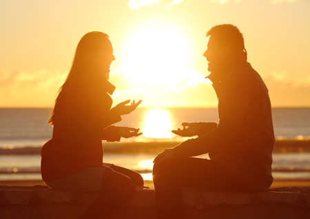 Side view of a couple silhouette together talking at sunrise on the beach with the sun in the middle Stock Photo